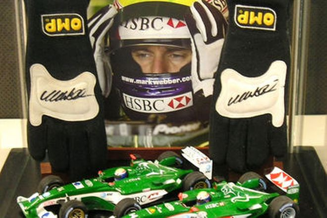 Display Case containing Mark Webber's Signed F1 OMP Gloves, 2 x Jaguar F1 Model Cars & Photo